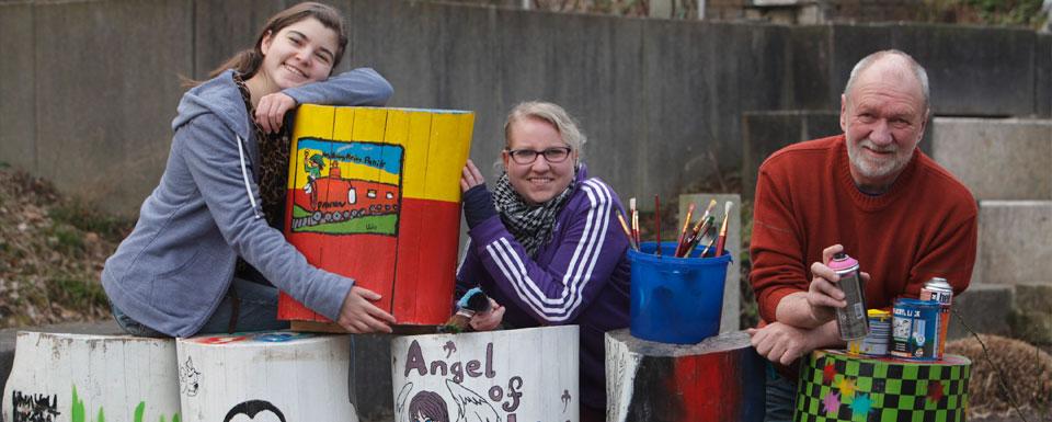 Junge Künstlerinnen mit Betreuer und bunt bemalten Holzstämmen